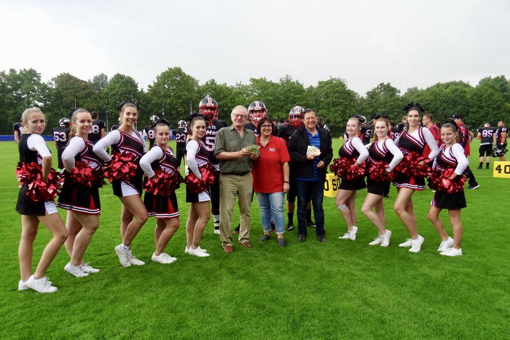 Spende 1: Andrea Michel (Mitte), Heinz Paula (Tierschutzverein, li), Norbert Krix (Hilfsfond, re), gerahmt von den ANTS Cheerleader und drei Spielern der ANTS